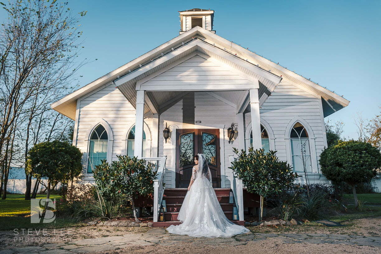 bride in front of white wedding chapel