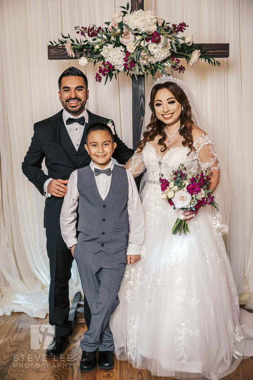 bride and groom with son after wedding ceremony