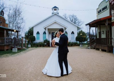 bride and groom in front of white wedding chapel